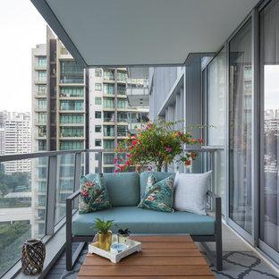 Immagine di un balcone d'appartamento design con un tetto a sbalzo e parapetto in materiali misti