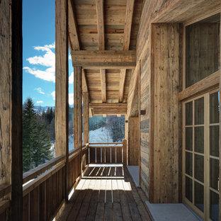 Idee per grandi terrazze e balconi stile rurale con un tetto a sbalzo e parapetto in legno