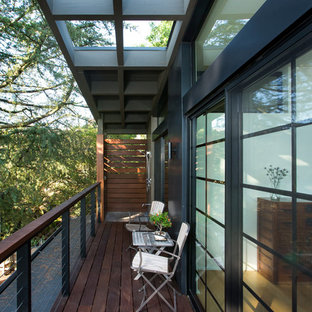 This is an example of a mid-sized midcentury balcony in Los Angeles with a roof extension, mixed railing and with privacy feature.