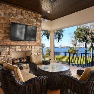 Стильный дизайн: большой балкон и лоджия в средиземноморском стиле с уличным камином, навесом и металлическими перилами - последний тренд