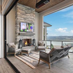 Inspiration pour un très grand balcon rustique avec une cheminée, une extension de toiture et un garde-corps en verre.
