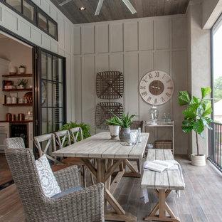 Ispirazione per terrazze e balconi tradizionali con un giardino in vaso, un tetto a sbalzo e parapetto in metallo