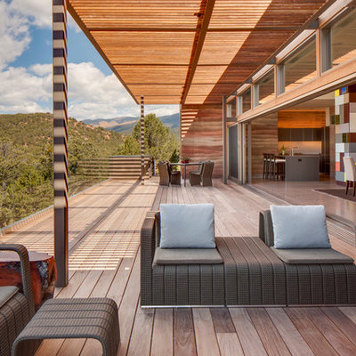 Inspiration for a large contemporary balcony remodel in Albuquerque with a roof extension