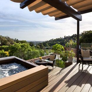 Ví dụ về thiết kế ban công lan can kính tuscan cỡ trung ở Los Angeles với một pergola