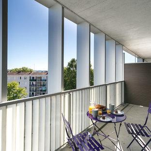 Aménagement d'une terrasse et balcon contemporaine avec une extension de toiture et un garde-corps en bois.