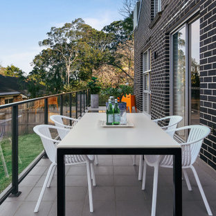 Contemporary balcony in Sydney with no cover and glass railing.