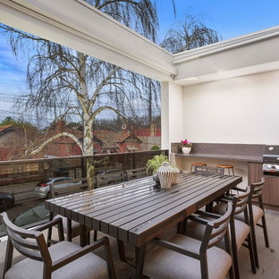 Idee per terrazze e balconi minimal con un parasole e parapetto in vetro