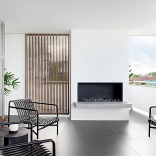 This is an example of a mid-sized contemporary balcony in Brisbane with with fireplace and a roof extension.