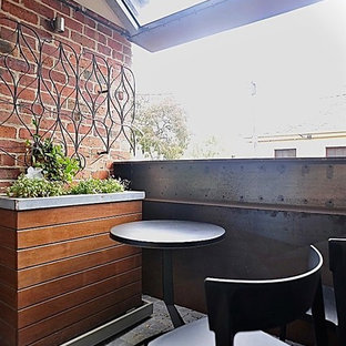 Inspiration for a small industrial metal railing balcony container garden remodel in Melbourne with a pergola