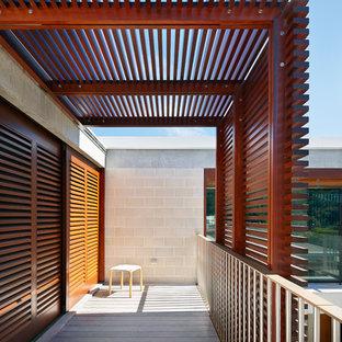 Exempel på en stor modern balkong insynsskydd, med en pergola