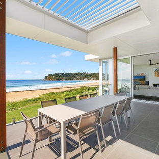 This is an example of a contemporary balcony in Central Coast with a roof extension.