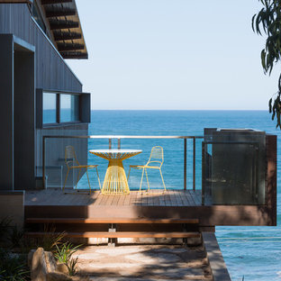 This is an example of a mid-sized beach style balcony in Geelong with glass railing and no cover.