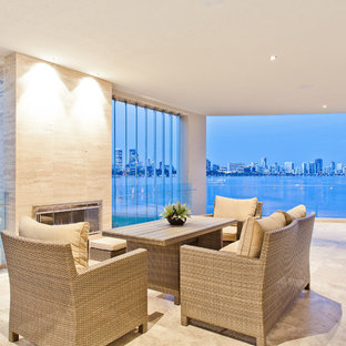 This is an example of a beach style balcony in Perth with a fire feature and a roof extension.