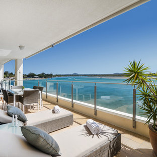 Design ideas for a beach style balcony in Sunshine Coast with a roof extension.