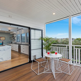 Inspiration for a beach style balcony in Sydney with a roof extension.