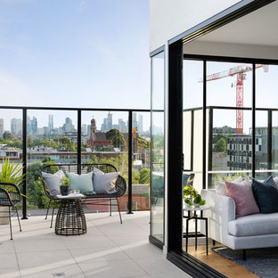 Inspiration for a contemporary balcony in Melbourne with no cover and glass railing.