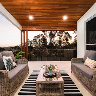 Photo of a beach style balcony in Brisbane with a roof extension and glass railing.