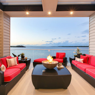 Photo of a contemporary balcony in Gold Coast - Tweed with a fire feature and a roof extension.