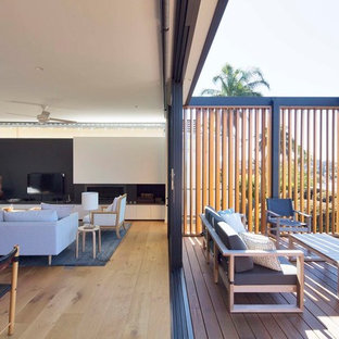 Mid-sized contemporary balcony in Sydney with no cover, glass railing and with privacy feature.
