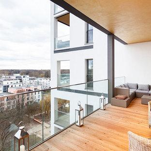 Cette photo montre une grande terrasse tendance avec une extension de toiture.