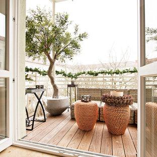 Inspiration pour une terrasse et balcon nordique de taille moyenne avec une extension de toiture.