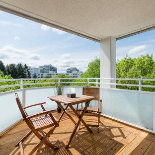 Mittelgroßer, Überdachter Moderner Balkon mit Mix-Geländer in München