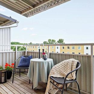 Cette image montre un balcon nordique avec des plantes en pot, une extension de toiture et un garde-corps en métal.
