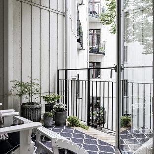 Cette photo montre une petite terrasse avec des plantes en pots scandinave avec une extension de toiture et un garde-corps en métal.