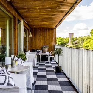 Minimalistisk inredning av en stor balkong, med utekrukor, takförlängning och räcke i metall