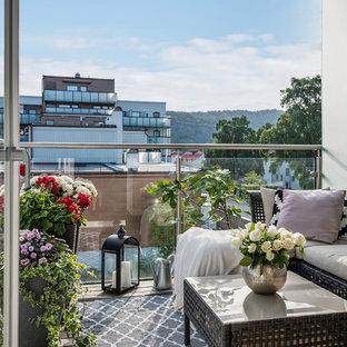 Inredning av en minimalistisk balkong, med utekrukor och räcke i glas