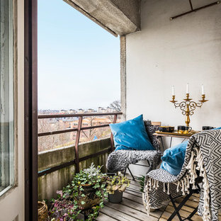 Esempio di piccoli terrazze e balconi boho chic con un giardino in vaso, un tetto a sbalzo e parapetto in materiali misti