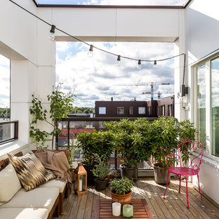 Photo of a large scandinavian terrace and balcony in Stockholm with a potted garden and no cover.