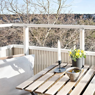 This is an example of a small scandinavian metal railing balcony in Stockholm with a potted garden and no cover.