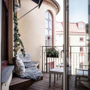 Foto på en liten nordisk balkong, med utekrukor, markiser och räcke i metall