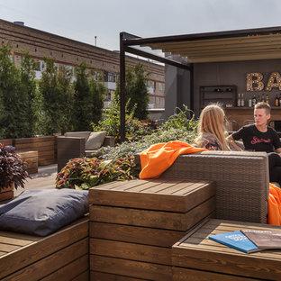 Неиссякаемый источник вдохновения для домашнего уюта: балкон и лоджия среднего размера в стиле лофт с растениями в контейнерах, навесом и деревянными перилами