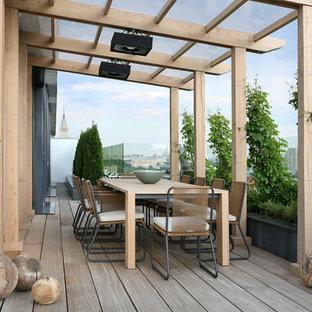 Exempel på en modern balkong, med en pergola och en vertikal trädgård