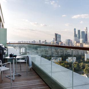 Стильный дизайн: балкон и лоджия в современном стиле с стеклянными перилами без защиты от солнца в квартире - последний тренд