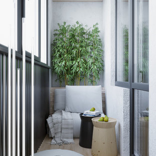 Photo of a small contemporary metal railing balcony in Valencia with a potted garden and a roof extension.