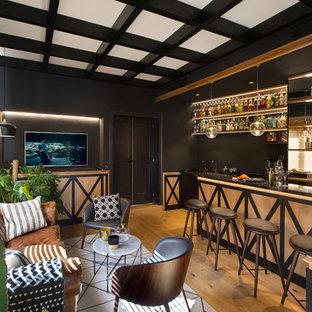 Diseño de bar en casa con barra de bar de galera, clásico renovado, con armarios con paneles con relieve, puertas de armario beige, salpicadero con efecto espejo, suelo de madera en tonos medios, suelo marrón y encimeras negras