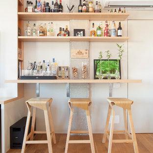 Modelo de bar en casa con barra de bar lineal, escandinavo, pequeño, con armarios abiertos, puertas de armario de madera clara, suelo de madera en tonos medios y suelo marrón