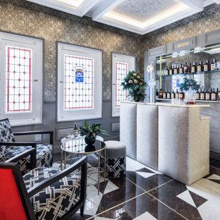 Modelo de bar en casa con barra de bar de galera, contemporáneo, de tamaño medio, con puertas de armario grises, salpicadero con efecto espejo, suelo multicolor y encimeras grises