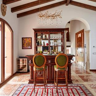 Imagen de bar en casa con barra de bar de galera, mediterráneo, con puertas de armario de madera en tonos medios, salpicadero con efecto espejo y suelo marrón