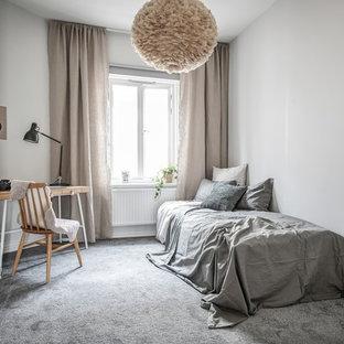 Foto på ett minimalistiskt könsneutralt barnrum kombinerat med sovrum, med vita väggar, heltäckningsmatta och grått golv