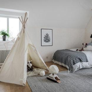 Idéer för ett nordiskt könsneutralt barnrum kombinerat med sovrum, med beige väggar, mellanmörkt trägolv och brunt golv