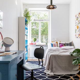 Idéer för ett mellanstort nordiskt könsneutralt barnrum kombinerat med sovrum, med vita väggar, mellanmörkt trägolv och brunt golv