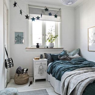 Minimalistisk inredning av ett barnrum kombinerat med sovrum, med vita väggar, målat trägolv och vitt golv