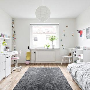 Inspiration för mellanstora moderna könsneutrala barnrum kombinerat med sovrum och för 4-10-åringar, med vita väggar och ljust trägolv