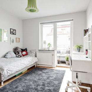 Inspiration för ett skandinaviskt könsneutralt barnrum kombinerat med sovrum, med grå väggar, mellanmörkt trägolv och brunt golv