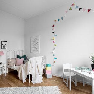 Idéer för att renovera ett nordiskt barnrum kombinerat med sovrum, med vita väggar, mellanmörkt trägolv och brunt golv