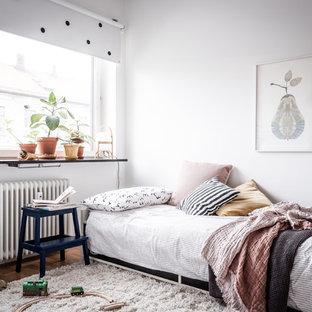 Idéer för skandinaviska könsneutrala barnrum, med vita väggar, mellanmörkt trägolv och brunt golv